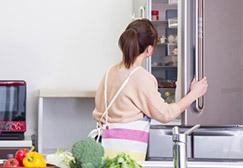 冷蔵庫を開ける女性の後姿 画像